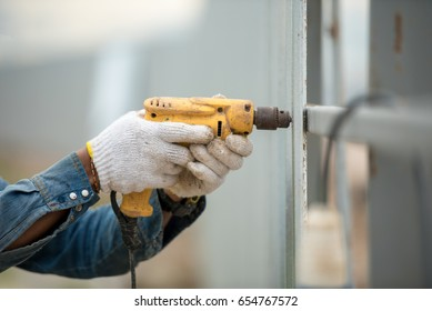 Foreman worker wearing helmet drilling fence wall home by electric drill in construction site