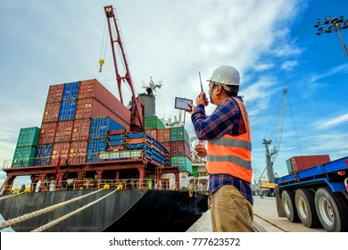 foreman working in port terminal for loading discharing with control status of operation report on line by devices mobile and radio walkie talkie to the clients customers at the jobsite