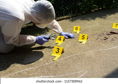 Forensic expert collects evidence at the crime scene. He studies the bullet shell caliber with the help of a magnifier