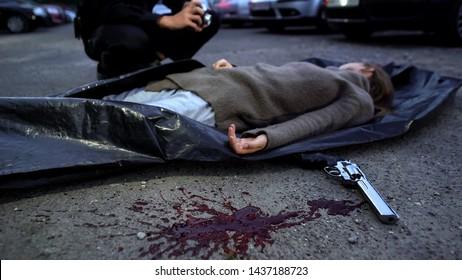 Forensic expert making photos of female corpse, crime scene murder investigation