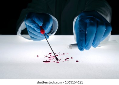 Forensic expert takes a blood sample with a sterile stick collecting evidence. Crime scene investigation concept.