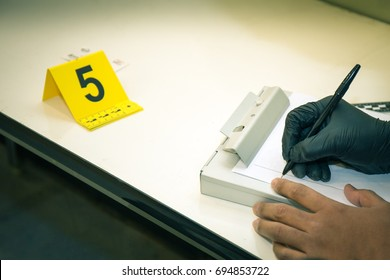 forensic hands in glove  writing evidence information with evidence marker in cinematic tone and copy space