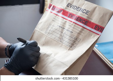 forensic 's hand in black glove writing on evidence bag and seal by red tape in crime scene investigation