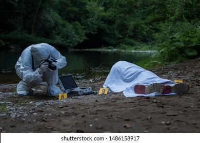 Forensic taking photo of victim.
