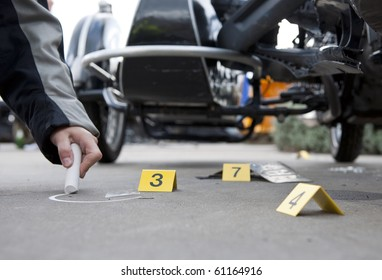 Forensics at the site of a car crash, with a policewoman's hand drawing a circle with chalk around a piece of glass
