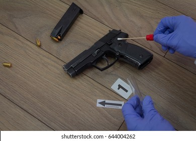 Forensics takes a DNA sample to sterile sticks with gun found at the crime scene