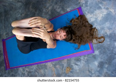 Foreshortened view looking down on attractive long haired woman on yoga mat stretching hamstrings in studio against a mottled background.