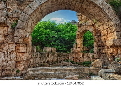 Forest behind a ruined archway at Perge Turkey