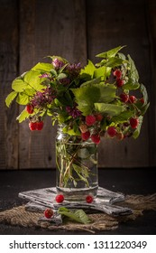 Forest berries with leaves on rustic background. a branch of raspberry in a glass jar. Summer harvest of berries. Still life in a rustic style