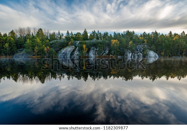Forest and cliffs mirrored in calm lake