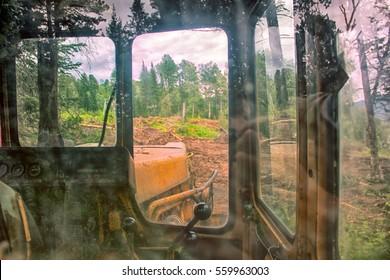 Forest cover destruction (deforestation). Forest and its annihilator (shredder). Abandoned in forest skidder and reflection of trees in glass. Concept