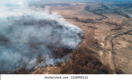 Forest and field fire. Dry grass burns, natural disaster. Aerial view. Flying over a smoking field, spring fall of grass.