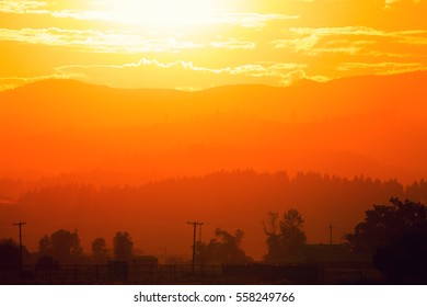 A forest fire fills the southern Willamette Valley with smoke, cloaking buildings, forests and hills with red and orange hues.