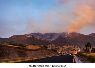 Forest fire on a mountain in the Ecuadorian Andes, next to a road.