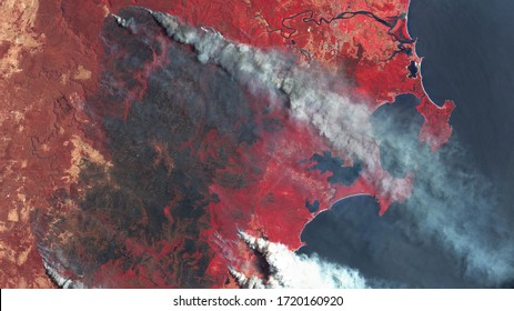 Forest fires in Australia, a view from space. Environmental problems, a large fire in the forest, burned-out section of forest. Satellite photo red tinting, contains modified Copernicus Sentinel data