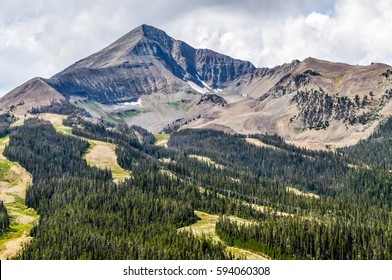 A forest flows downward from the high rocky top of Lone Peak in Montana.