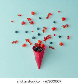 Forest fruit with ice cream cone on blue pastel background. Flat lay. Summer concept.