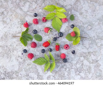 Forest fruits: strawberry raspberry whortleberry and leafin the concrete background