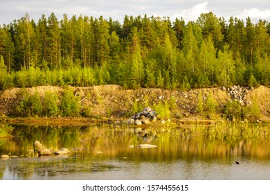 Forest lake, mound of boulders and deciduous forest on the background. Summer landscape.