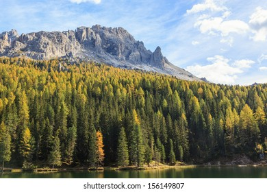 Forest lake and mountain peak in autumn