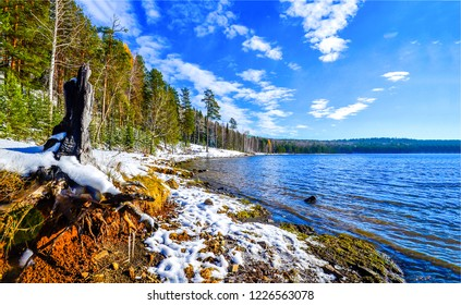 Forest lake shore snow landscape. Forest lake snow scene. Forest lake shore in snow. Snowy forest lake shore view