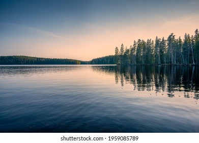 Forest lake in Sweden on a spring late afternoon, after sunset. Bredsjön lake in Stjärnfors under a blue-pink soothing sky. Relaxing nature image. Explore Scandinavia.