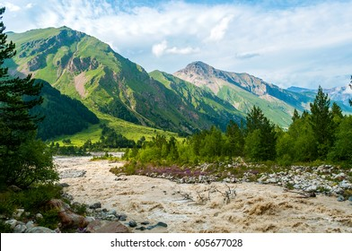 Forest, mountain river, mountain slopes and mountain peaks. Narzan valley, North Caucasus, Kabardino-Balkaria.against the background of clouds and blue sky.