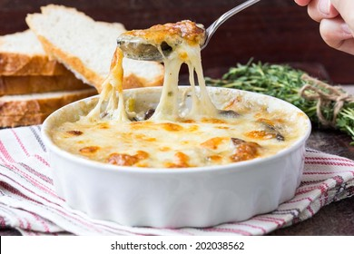 Forest mushrooms gratin , white, orange brown cap boletus with cream, cheese, French dish julienne