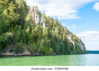 Forest on the bank of the lake . White clouds reflect in the water