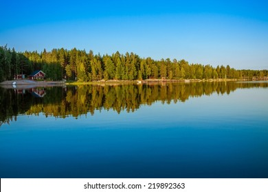 Forest reflecting on calm lake shore, Finland