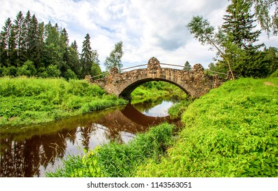 Forest river stone bridge landscape. Ancient bridge river stone view. Medieval bridge river forest scene