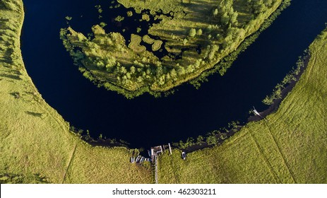 Forest river watercourse in marsh. Wooden rowboats moored on the shore. Aerial view. Northern Karelia, Russia