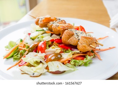 Forest salad with chicken skewers souvlaki on a white plate on a sunny day