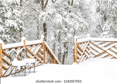Forest, snow covered house, home wooden deck with two cast iron chairs, snowing, falling snowflakes, snowstorm, storm, trees in backyard, front yard, railing, fence in winter with nobody