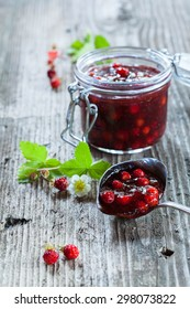 Forest strawberry jam in a jar on rustic wooden background