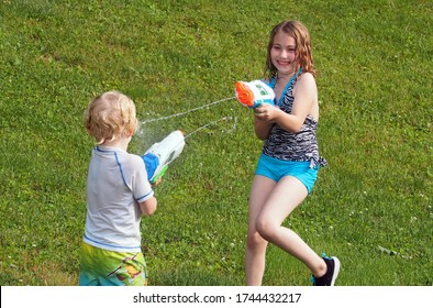 Forest, Virginia / USA - May 29, 2020:  A brother and sister cooling off by battling with super soakers in a backyard in Forest, Virginia.