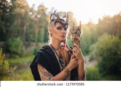 A forest witch with a staff in the form of a spine. Beautiful girl in the forest in a black raincoat and with a crown