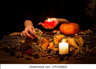 Forest witch at work on the altar. Female hands with sharp red nails among candles, herbs, pumpkin, nuts, dry leaves, ashberry, selected focus, low key. Halloween, Samhain night, autumn, magic