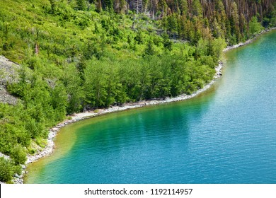 Forested shore line of Saint Mary Lake in Glacier National Park, Montana, USA