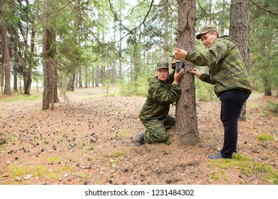 Foresters install photo traps on a tree for automatic photographing or video shooting of wildlife in the forest.