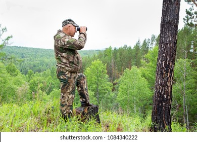 Foresters went to the protection of the forest. An adult male forester examines the forest from the top of the mountain through binoculars. The huntsman shows the directions of the brown bear habitat.