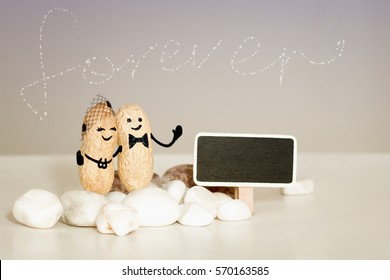 Forever love idea. Two peanuts with drawn faces hugging on pink vanilla background. Family, love, wedding, anniversary, travel honeymoon or taking care concept. Template mock up chalkboard copy space