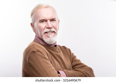 Forever young. The portrait of a charming senior man with a white beard and an earring in his ear standing half-turned and posing isolated on a white background