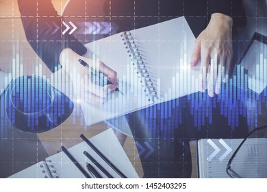 Forex chart hologram on hand taking notes background. Concept of analysis. Multi exposure