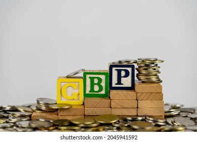Forex GBP concept with wooden blocks and coins. Forx GBP letters on wooden blocks sorrounded with money