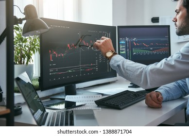 Forex market. Young trader is pointing at graphs on computer screen and analyzing data while working in his modern office.