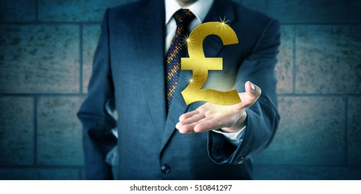 Forex trader holding a golden British Pound Sterling symbol in the open palm of his left hand. Business concept and financial services metaphor for interbank market, currency, wealth and achievement.