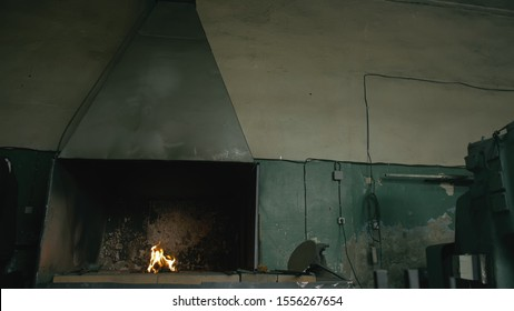 Forge fire in furnace. Blacksmith tempers a steel product in a stove. Smithy forging for hardening and heating iron. Blacksmith makes iron for manufacture of fireplace, stove. Burner Slow Motion.