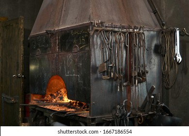 forge furnace with burning flame and blacksmith tools