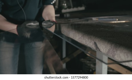 Forge. Smithy. Glass cutting and processing for fireplace doors. Circular glass cutter. Worker cut glass with glass cutting diamond. Polish an angle grinder with an abrasive circular disk nozzle.
